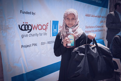 A Yemeni girl receives a family hygiene kit, packed with items such as disinfectant, handwash, nappies and sanitary pads.