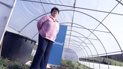 on of the beneficiaries of breaking poverty trap projects, standing in her greenhouse