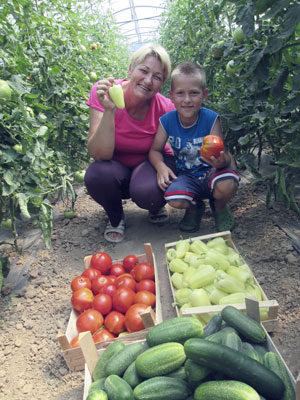 a woman and boy laughing in their greenhourse in front of them some vegetables, fighting poverty trap