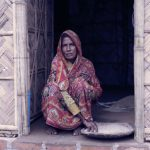 a woman wearind indian uniform and sitting in a flood resistant homes