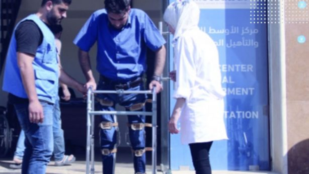 A nurse with a disabled refugee trying to walk with a chair during a physical therapy session